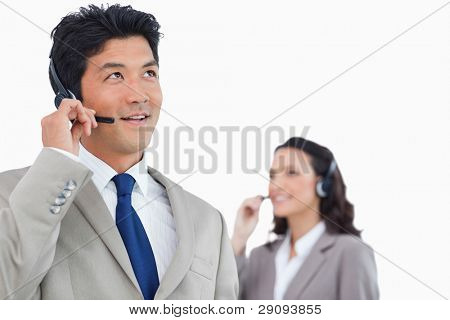Call center agent with headset and colleague behind him against a white background