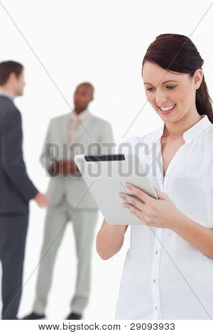 Saleswoman with tablet and associates behind her against a white background