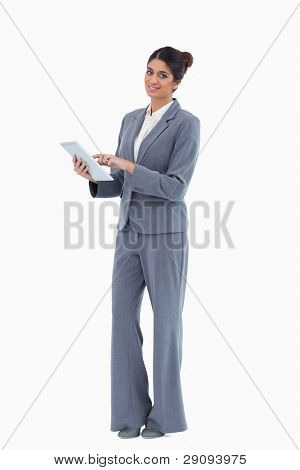 Smiling saleswoman using tablet against a white background