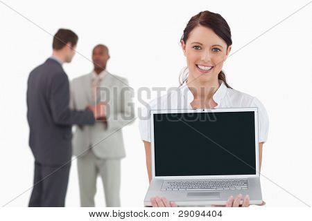 Tradeswoman showing notebook with colleagues behind her against a white background