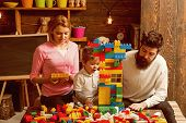 Play Concept. Learn Through Play. Little Son With Mother And Father Play With Toy Bricks. Creative F poster