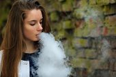 Vape Teenager. Young Pretty White Girl In White Cardigan Smoking An Electronic Cigarette Opposite De poster