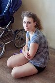 Tired Sad Mother Sits On The Floor Near The Stroller, Parenthood Difficulties, Postpartum Depression poster