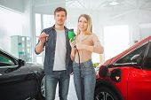 Young Smiling Family Buying First Electric Car In The Showroom. Environmental Protection. Attractive poster