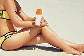 Closeup On Female Hand Applying Sun Screen Creme On Leg. Skincare.  Sun Protection Sun Cream, On Her poster