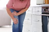 Senior Woman Suffering From Knee Pain In Kitchen, Closeup. Space For Text poster