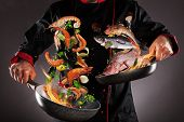 Closeup of chef throwing sea fruit and fish into the air, fire flames around. Concept of food prepar poster