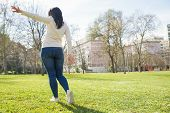 Young Woman Resting In City Park. Rear View Of Girl In Casual Walking On Grass. Walking In City Park poster