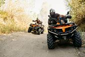Two quad bike riders travels in forest, front view poster