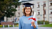 graduation, education and old people concept - happy senior graduate student woman in mortar board w poster