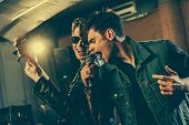 Stylish Singer Singing In Microphone With Handsome Guitarist In Sunglasses poster