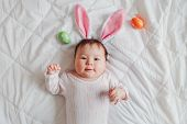 Cute Adorable Mixed Asian Baby Wearing Pink Easter Bunny Ears Lying On Bed In Bedroom With Colorful  poster