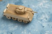 Wooden tank on white and blue painting surface. Wooden toy tank and piece of fine art studio shot. poster