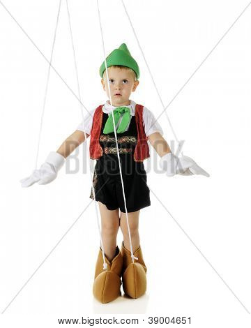 An adorable preschooler playing the puppet Pinocchio, strings and all.  On a white background.