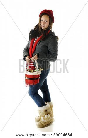 A pretty presteen in outdoor winter-wear carrying a basket of Christmas ornaments.  On a white background.