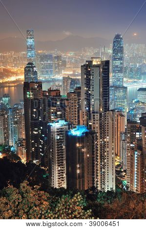 Hong Kong city skyline at night with Victoria Harbor and skyscrapers illuminated by lights over water viewed from mountain top.