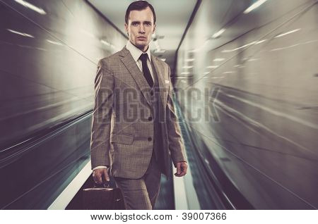 Man in classic grey suit with briefcase standing on escalator