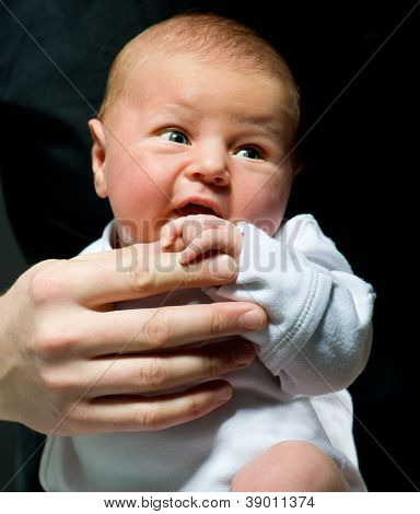 father holding his newborn daughter over black background