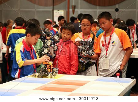 SUBANG JAYA - NOVEMBER 10: Unidentified elementary students prepare their robot for the 'robot organizer' challenge at the World Robot Olympaid on November 10, 2012 in Subang Jaya, Malaysia.