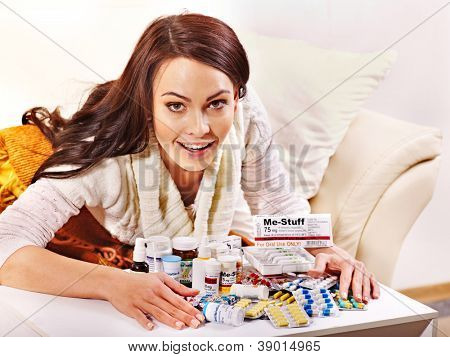 Woman with remedy having  flue in bed. Indoors.