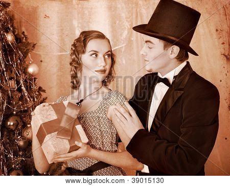 Couple on party near Christmas tree. Black and white retro.