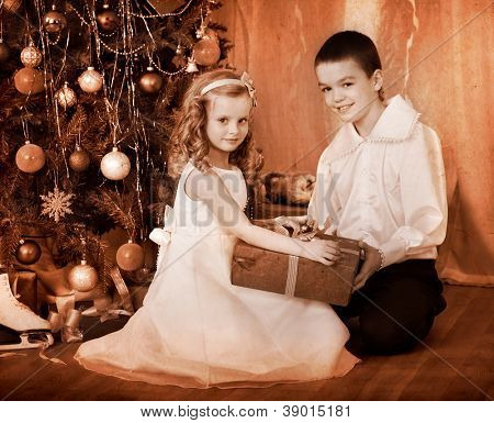 Children  receiving gifts under Christmas tree. Black and white retro.
