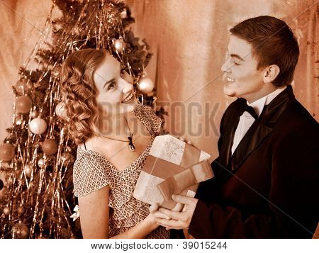 Couple on party near Christmas tree. Black and white retro.