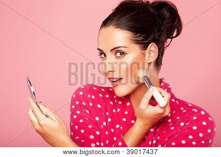 Linda jovem morena, aplicando blush para sua bochecha usando uma escova cosmética e compac pequeno