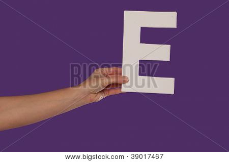 Female hand holding up the uppercase capital letter E isolated against a purple background conceptual of the alphabet, writing, literature and typeface