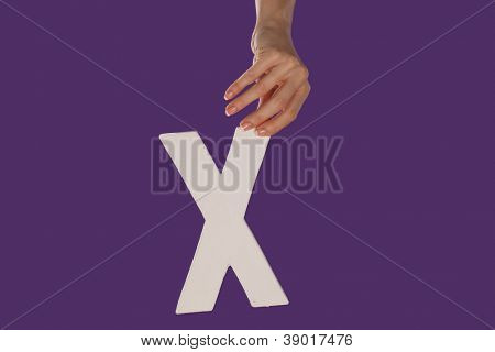 Female hand holding up the uppercase capital letter A isolated against a purple background conceptual of the alphabet, writing, literature and typeface