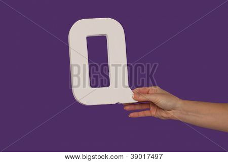 Female hand holding up the uppercase capital letter Q isolated against a purple background conceptual of the alphabet, writing, literature and typeface