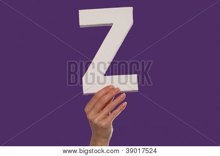 Female hand holding up the uppercase capital letter Z isolated against a purple background conceptual of the alphabet, writing, literature and typeface
