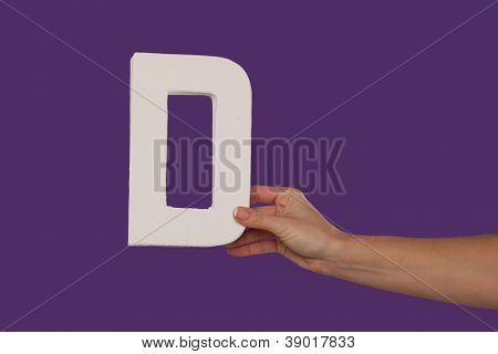 Female hand holding up the uppercase capital letter D isolated against a purple background conceptual of the alphabet, writing, literature and typeface