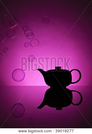 Teapot silhouetted against pink background, soap bubbles floating around
