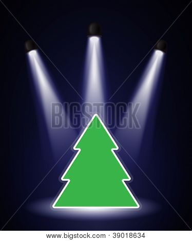 A Christmas tree shape in the spotlight with space for your text. Also available in vector format.