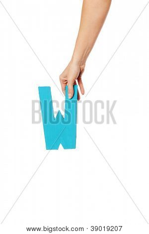 Female hand holding up the uppercase capital letter W isolated against a white background conceptual of the alphabet, writing, literature and typeface
