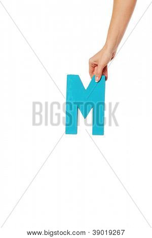 Female hand holding up the uppercase capital letter M isolated against a white background conceptual of the alphabet, writing, literature and typeface