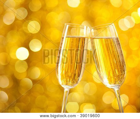 Two glasses of champagne with lights in the background. very shallow depth of field.