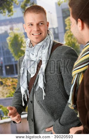 Smiling young men talking outside, wearing trendy spring clothes.