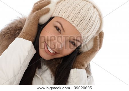 Winter portrait of smiling young woman in white cap and earmuffs.