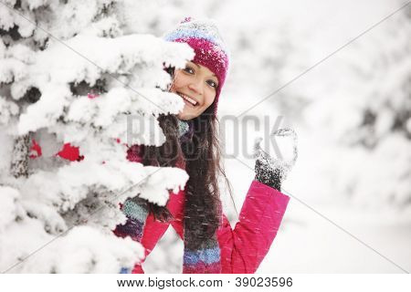 winter woman play snowballs on snow background