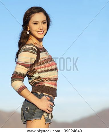 Pretty young woman wearing stylish cut denim shorts and sweater with blue sky and desert mountains in background