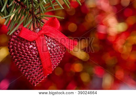 Heart-shape ornament hanging on the fir branch with red-golden bokeh effect in the background