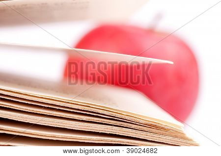 Macro shot of a book pages and blurred apple in the background, isolated on white