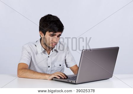 young man surfing the internet in his laptop sited on the carpet (isolated on white)