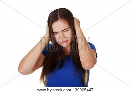Closeup of frustrated young woman holding her ears, isolated on white
