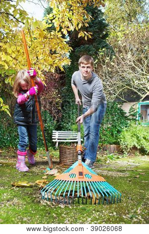Father and daughter raking autumn leaves in the backyard
