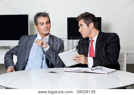 Two businessmen using digital tablet at desk in office