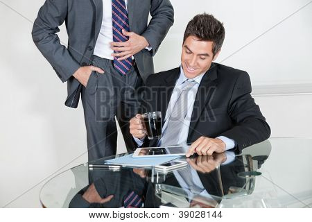 Businessman using digital tablet in a meeting with colleague at office