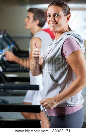 Side view of happy mature woman and man running on treadmill in health club